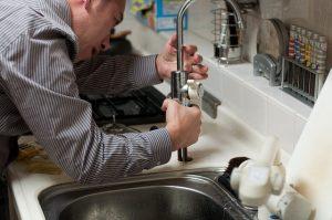 Artisan plombier qui répare un évier